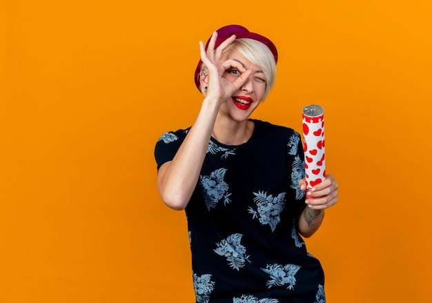 Impressed young blonde party girl wearing party hat looking at camera holding confetti cannon doing look gesture isolated on orange background with copy space