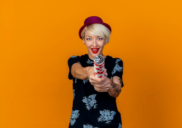 Impressed young blonde party girl wearing party hat looking at camera stretching out confetti cannon towards camera isolated on orange background with copy space