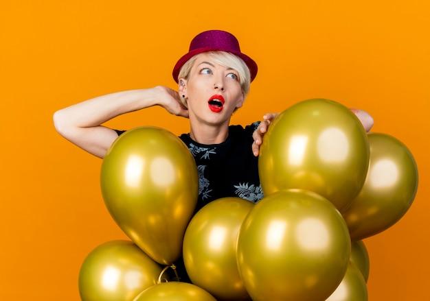 Impressionato giovane bionda party girl indossando il cappello del partito in piedi dietro i palloncini tenendo la mano dietro il collo e sul palloncino guardando il lato isolato su sfondo
