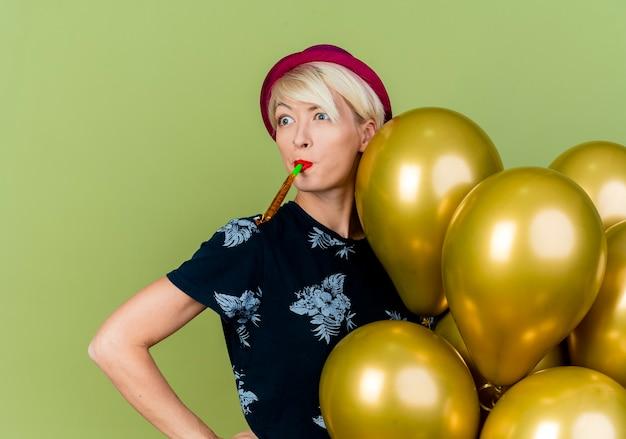 Impressionato giovane ragazza bionda party indossando il cappello del partito in piedi dietro i palloncini mantenendo la mano sulla vita guardando il ventilatore di partito di soffiaggio laterale isolato su sfondo verde oliva