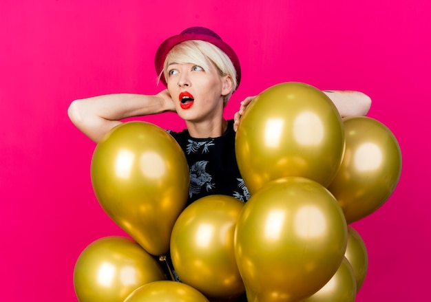 Impressed young blonde party girl wearing party hat standing behind balloons putting hand on one of them keeping hand behind head looking at side isolated on crimson background