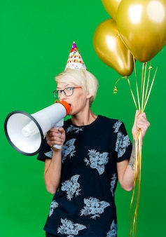녹색 벽에 고립 된 스피커에 의해 얘기를 앞에보고 풍선을 들고 안경과 생일 모자를 쓰고 감동 젊은 금발 파티 여자