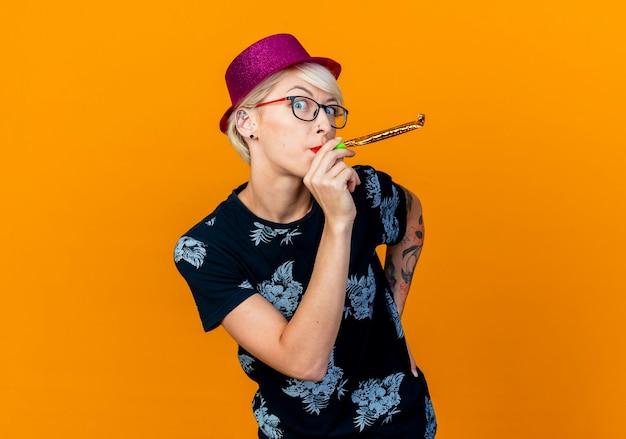 오렌지 벽에 고립 된 허리 불고 파티 송풍기에 손을 유지 앞에보고 파티 모자와 안경을 착용하는 감동 된 젊은 금발 파티 여자