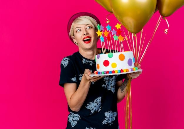 Impressionato giovane donna bionda festa indossando il cappello del partito che tiene palloncini e torta di compleanno con le stelle guardando la torta isolata sulla parete cremisi