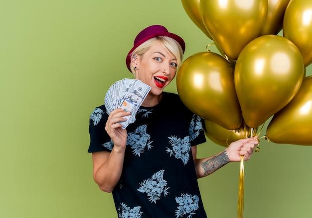 Impressionato giovane donna bionda del partito che indossa il cappello del partito che tiene palloncini e soldi che esaminano la parte anteriore isolata sulla parete verde oliva con lo spazio della copia