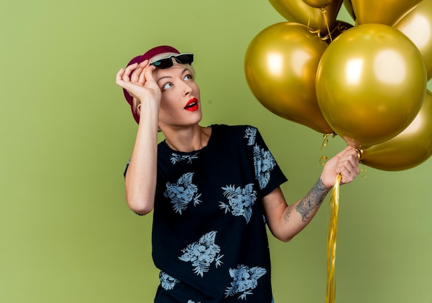Impressionato giovane donna bionda festa indossando cappello da festa e occhiali da sole alzando gli occhiali guardando palloncini isolati sulla parete verde oliva