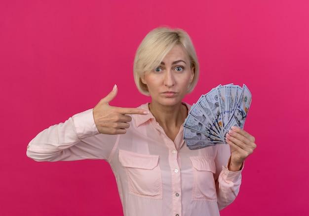 ピンクの背景に分離されたお金を保持し、指さしている印象的な若いブロンドのスラブ女性