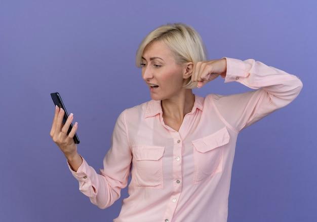 Impressionato giovane bionda donna slava che tiene guardando il telefono cellulare e il pugno di serraggio isolato su sfondo viola