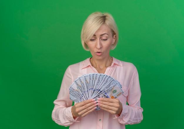 Impressionato giovane donna slava bionda che tiene e guardando i soldi isolati su sfondo verde con copia spazio