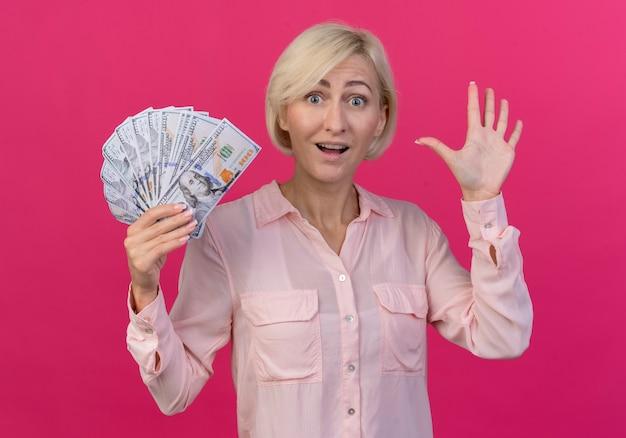 お金を保持し、ピンクの背景に分離された手でこんにちはジェスチャーをしている印象的な若いブロンドのスラブ女性
