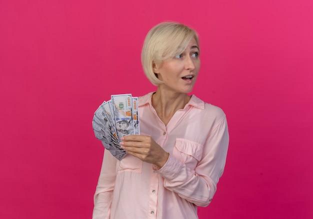 お金を保持し、コピースペースでピンクの背景に分離された側を見て感動の若い金髪スラブ女性