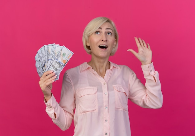 Impressionato giovane donna slava bionda che tiene i soldi che mostrano la mano vuota e che osserva in su isolato su fondo rosa