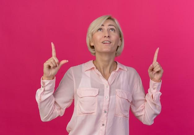 ピンクの背景に分離された見ていると上向きの印象的な若いブロンドのスラブ女性