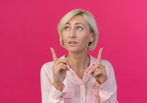 Impressed young blonde slavic woman looking and pointing up isolated on pink background with copy space