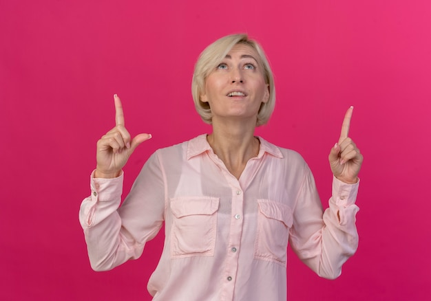 Impressionato giovane donna slava bionda alla ricerca e rivolto verso l'alto isolato su sfondo rosa