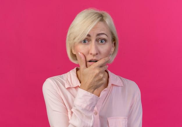 Impressionato giovane bionda donna slava mettendo la mano sul mento e guardando la telecamera isolata su sfondo rosa