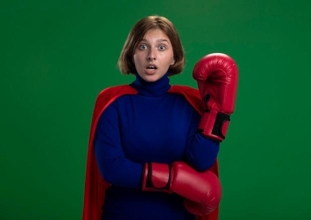 Впечатленная молодая белокурая женщина-супергерой в красном плаще в перчатках коробки держит руку в воздухе, глядя на фронт, изолированную на зеленой стене с копией пространства
