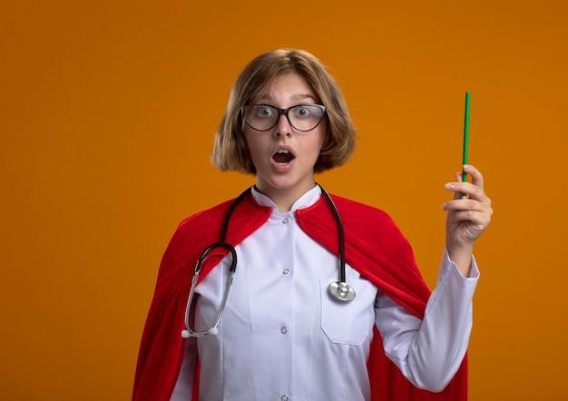 Impressionato giovane donna bionda supereroe in mantello rosso che indossa l'uniforme del medico e occhiali con lo stetoscopio che tiene la matita guardando la parte anteriore isolata sulla parete arancione con lo spazio della copia