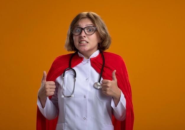 Impressionato giovane donna bionda supereroe in mantello rosso che indossa l'uniforme del medico e occhiali con lo stetoscopio guardando la parte anteriore che mostra i pollici in su isolato sulla parete con lo spazio della copia