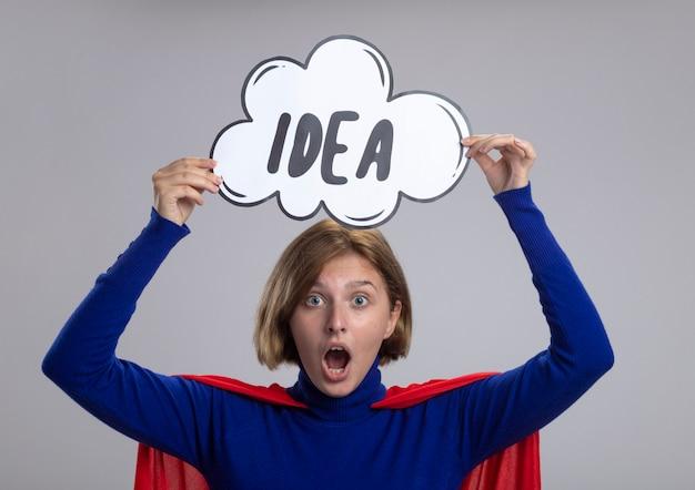 白い壁に分離された正面を見て頭の上にアイデアの泡を保持している赤いマントの印象的な若いブロンドのスーパーウーマン