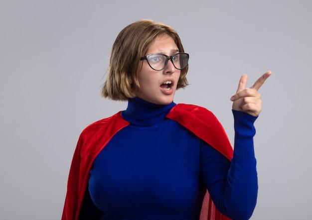 Впечатленная молодая блондинка суперженщина в красном плаще в очках смотрит и указывает на сторону, изолированную на белой стене