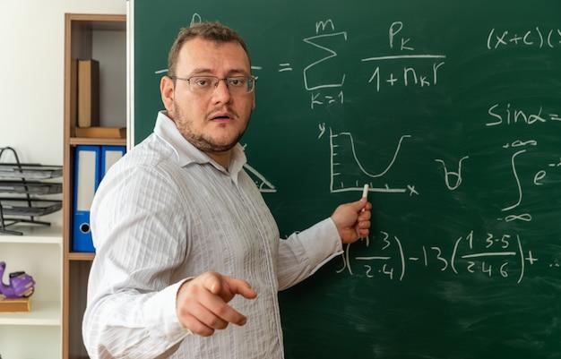 Impressionato giovane insegnante bionda con gli occhiali in piedi nella vista di profilo davanti alla lavagna in aula guardando e puntando la telecamera che puntando alla lavagna con il gesso