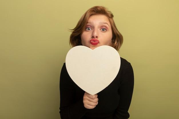 Impressionata giovane donna bionda che tiene a forma di cuore guardando davanti facendo gesto di bacio isolato su parete verde oliva con spazio di copia copy