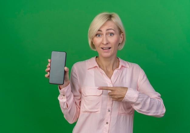 Впечатленная молодая блондинка показывает и указывая на мобильный телефон