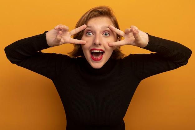 オレンジ色の壁に隔離された正面を見てピースサインをしている顔に触れている印象的な若いブロンドの女性