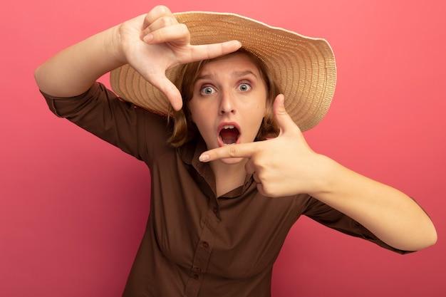 Впечатленная молодая блондинка в пляжной шляпе, глядя на фронт, делая жест кадра, изолированный на стене