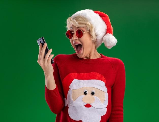 크리스마스 모자와 산타 클로스 크리스마스 스웨터를 입고 감동 된 젊은 금발의 여자 안경 들고 녹색 배경에 고립 된 휴대 전화를보고