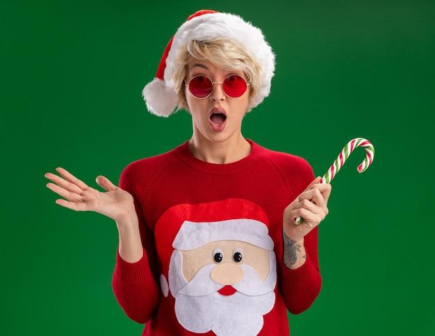 緑の背景に分離された空の手を示すカメラを見てクリスマスキャンディケインを保持しているメガネとクリスマス帽子とサンタクロースのクリスマスセーターを身に着けている印象的な若いブロンドの女性