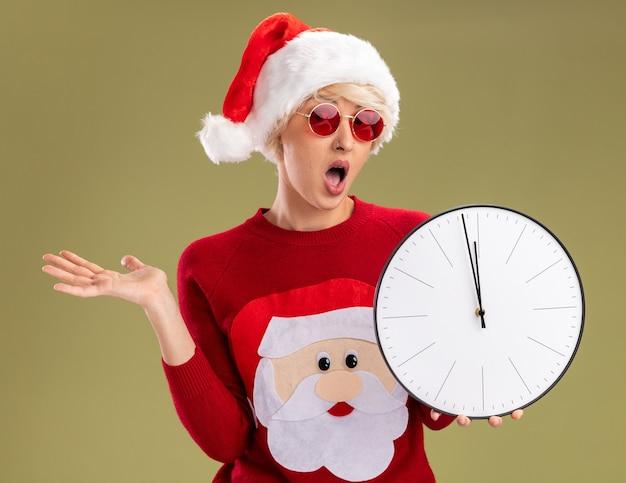 クリスマスの帽子とサンタクロースのクリスマスセーターを着て、オリーブグリーンの背景に分離された空の手を示すカメラを見て時計を保持している印象的な若いブロンドの女性
