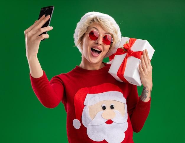 녹색 배경에 고립 된 셀카를 복용 어깨에 선물 패키지를 들고 안경 크리스마스 모자와 산타 클로스 크리스마스 스웨터를 입고 감동 젊은 금발의 여자
