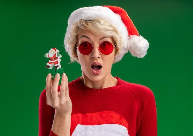 녹색 배경에 고립 된 카메라를보고 산타 클로스 장난감을 들고 안경 크리스마스 모자와 산타 클로스 크리스마스 스웨터를 입고 감동 젊은 금발의 여자
