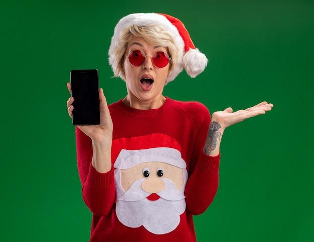 緑の背景に分離された空の手を示すカメラを見てカメラに携帯電話を示す眼鏡とクリスマス帽子とサンタクロースのクリスマスセーターを身に着けている感動の若いブロンドの女性