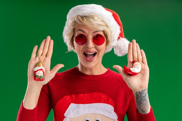 Impressed young blonde woman wearing christmas hat and santa claus christmas sweater with glasses looking  showing snowman and santa claus christmas ornaments  isolated on green wall