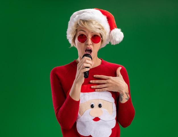 Impressionato giovane donna bionda che indossa cappello di natale e maglione di natale di babbo natale con gli occhiali che parla nel microfono tenendo la mano sul petto guardando isolato sul muro verde con spazio di copia