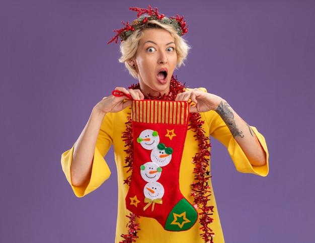紫色の背景に分離されたカメラを見てクリスマスの靴下を保持している首の周りにクリスマスのヘッドリースと見掛け倒しの花輪を身に着けている印象的な若いブロンドの女性