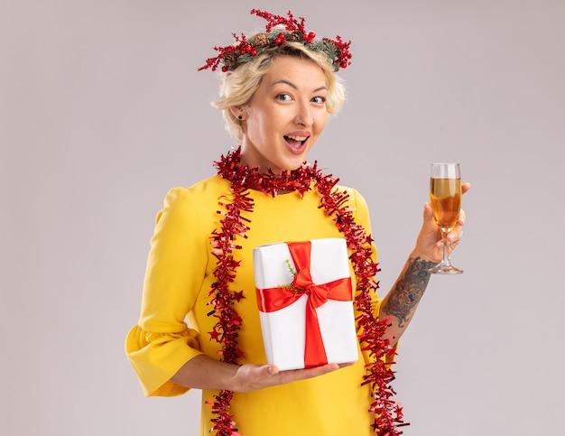 Impressionato giovane donna bionda che indossa la testa di natale ghirlanda e orpello ghirlanda intorno al collo tenendo un bicchiere di champagne e confezione regalo guardando la telecamera isolata su sfondo bianco