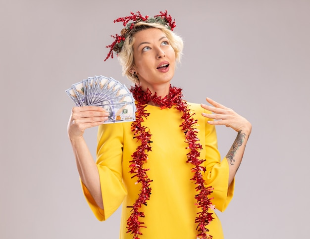 Impressionato giovane donna bionda che indossa la testa di natale ghirlanda e orpello ghirlanda intorno al collo tenendo i soldi tenendo la mano in aria cercando isolati su sfondo bianco