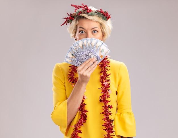 Impressionato giovane donna bionda che indossa la corona della testa di natale e la ghirlanda di orpelli intorno al collo che tiene i soldi che guardano da dietro isolato sul muro bianco con lo spazio della copia