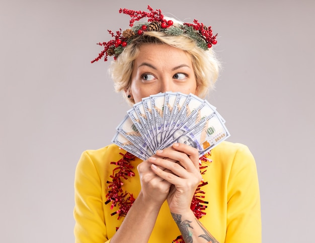 Impressed young blonde woman wearing christmas head wreath and tinsel garland around neck holding money looking at side from behind it isolated on white wall