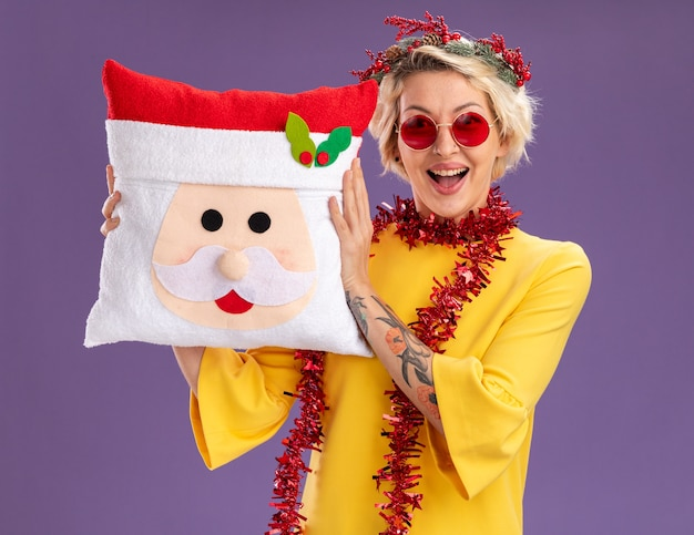Impressed young blonde woman wearing christmas head wreath and tinsel garland around neck holding santa claus pillow looking at camera isolated on purple background