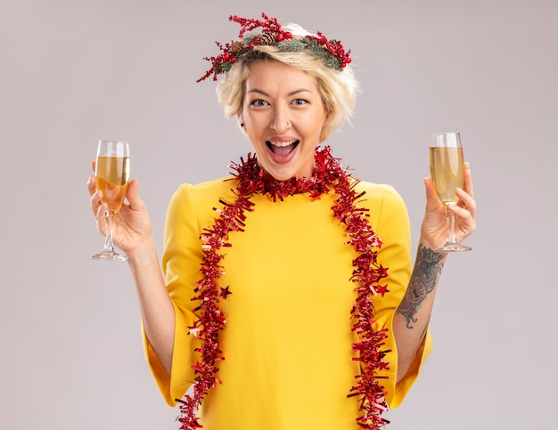 Impressed young blonde woman wearing christmas head wreath and tinsel garland around neck holding two glasses of champagne looking at camera isolated on white background