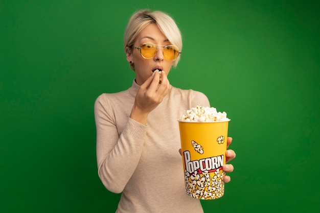 Impressed young blonde woman wearing sunglasses holding bucket of popcorn and popcorn pieces near mouth looking at side isolated on green wall with copy space