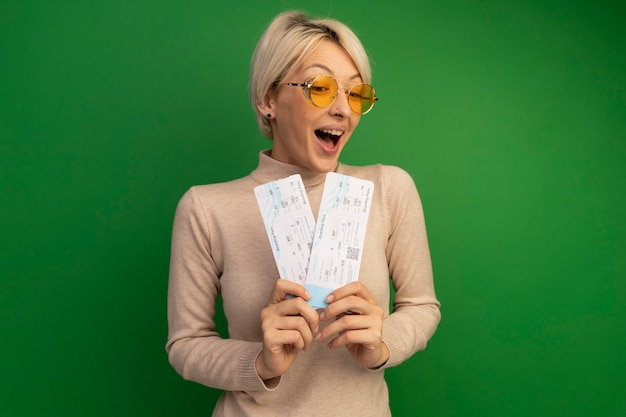 Impressed young blonde woman wearing sunglasses holding and looking at airplane tickets looking at front isolated on green wall with copy space