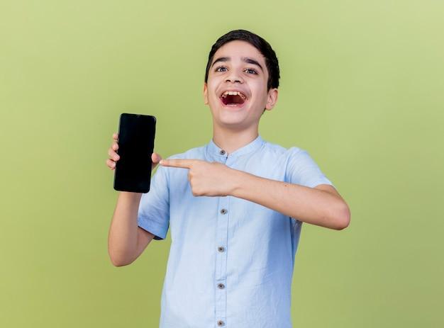 Ragazzo giovane impressionato che tiene e che indica al telefono cellulare che esamina la parte anteriore isolata sulla parete verde oliva