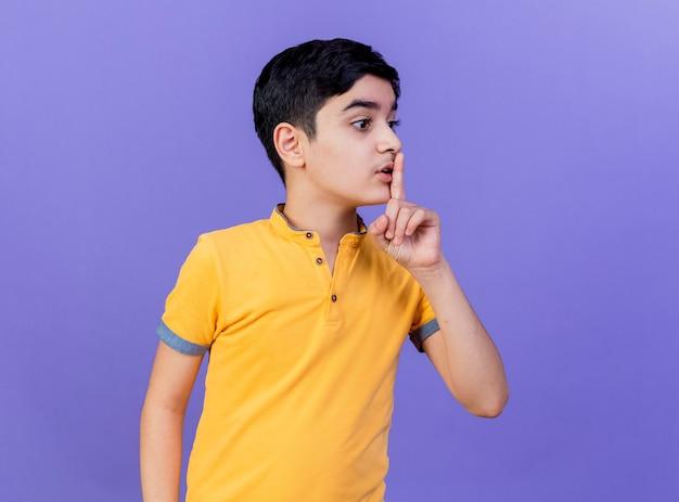 Впечатленный молодой мальчик, глядя в сторону, делая жест молчания, изолированный на фиолетовой стене
