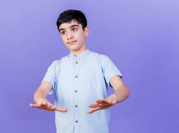 보라색 벽에 고립 된 앞쪽으로 손을 뻗어 측면을보고 감동 어린 소년